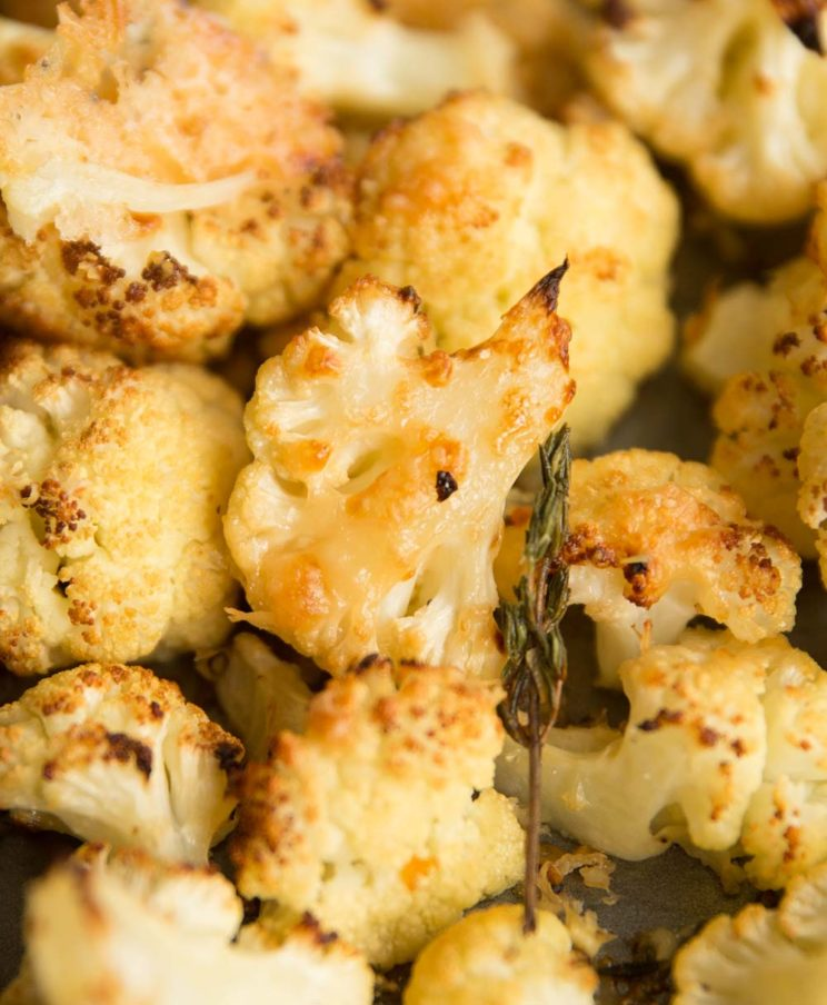 closeup shot of parmesan roasted cauliflower on baking tray with thyme