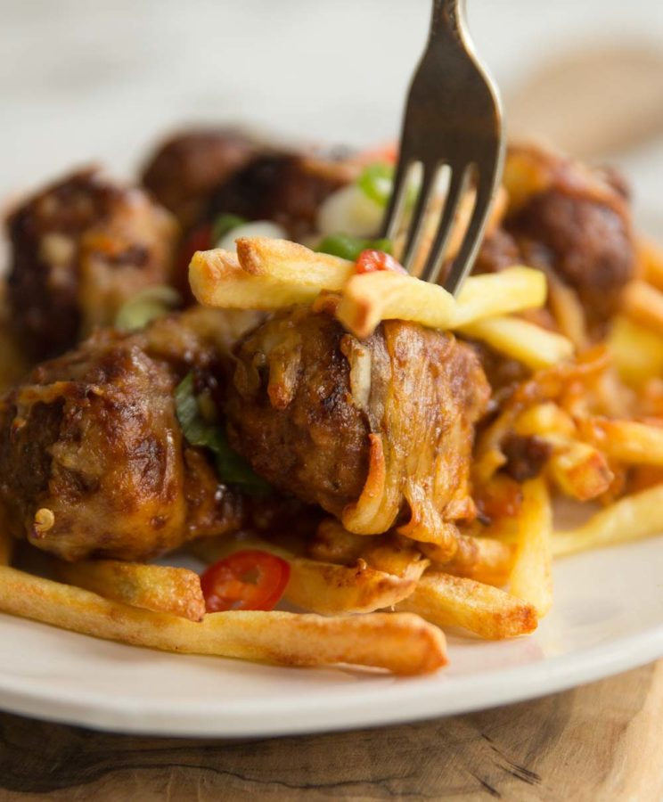 closeup of stabbing fork into meatball and fries
