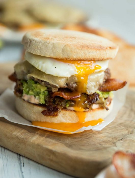 breakfast burger with yolk dripping down on chopping board