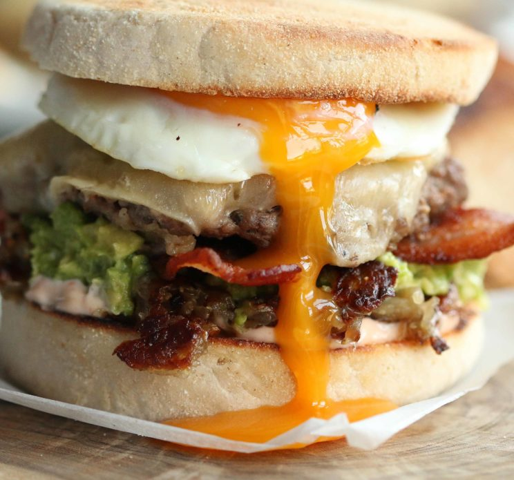 closeup of burger with egg yolk pouring down the centre
