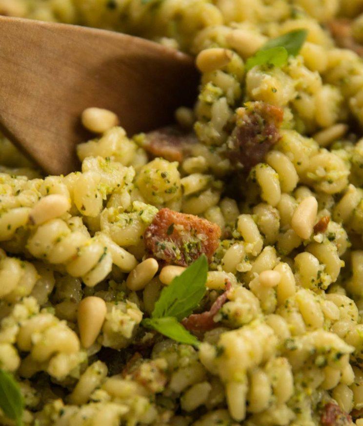 closeup shot of broccoli pesto pasta, focus on slice of bacon