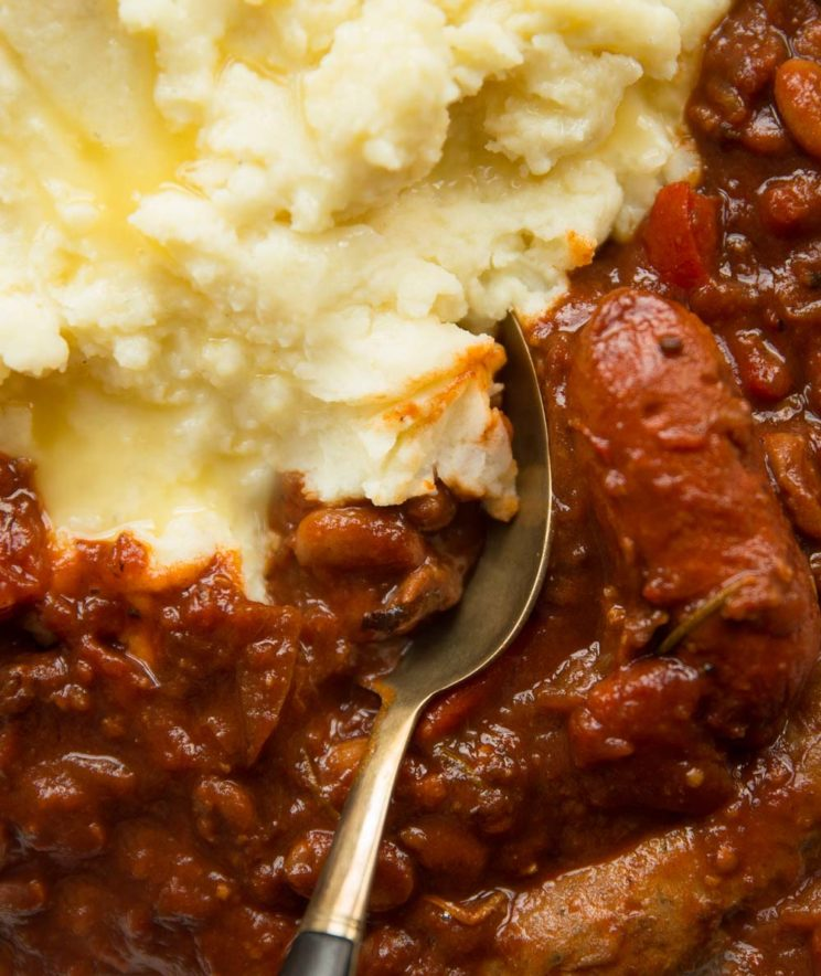 overhead shot of sausage and bean casserole with mashed potato and spoon digging in