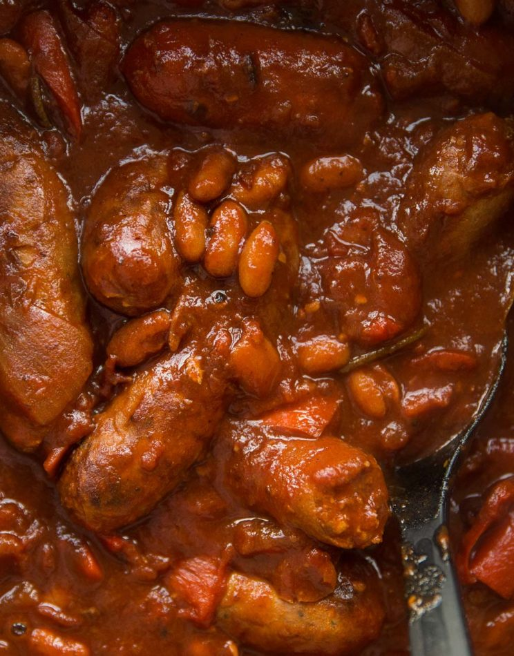 overhead shot of sausage casserole in pot with serving spoon digging in
