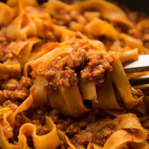 pasta tongs twirling sausage ragu in pan