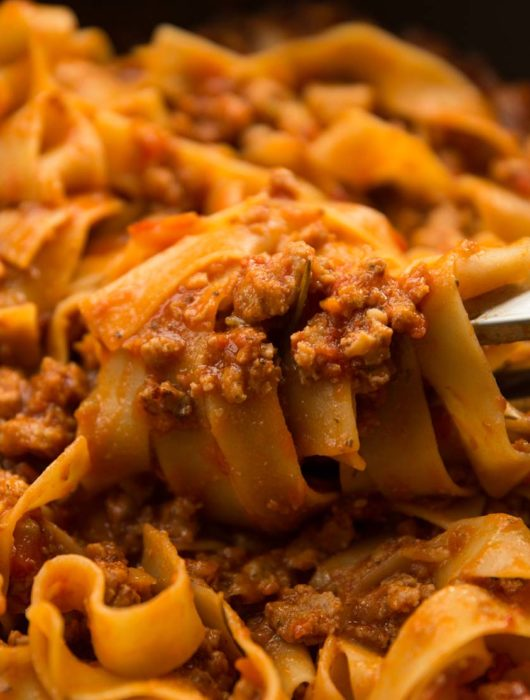pasta tongs twirling sausage ragu in pan