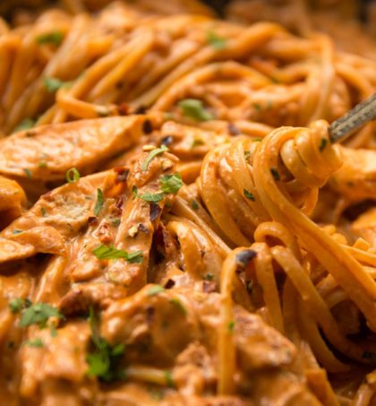 fork twizzling into chicken pasta in skillet