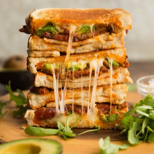 halloumi grilled cheese sandwich stacked on wooden board surrounded by rocket