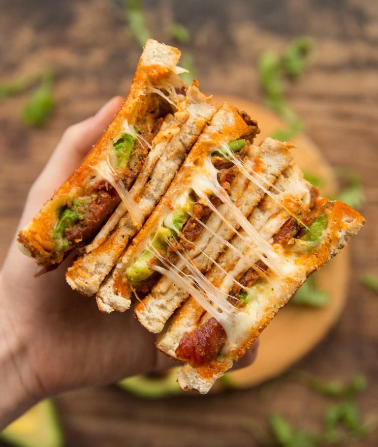 holding chorizo grilled cheese to camera showing filling with ingredients blurred behind