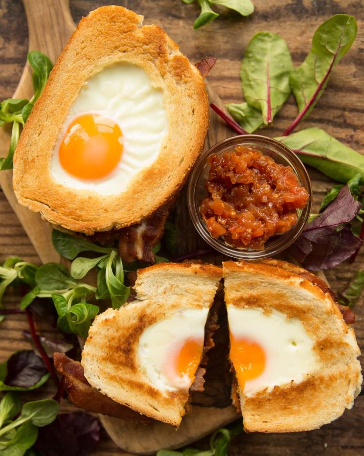 overhead shot of two egg in hole sandwiches with chutney and salad to garnish