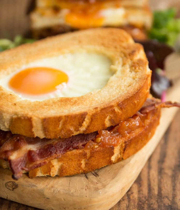 closeup shot of bacon sandwich on wooden board