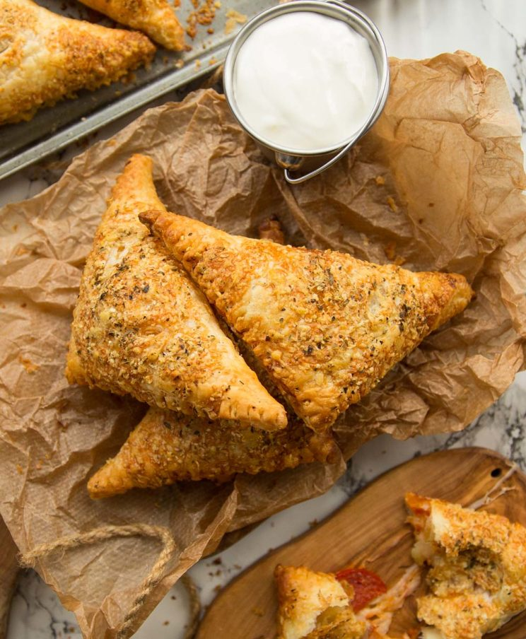 overhead shot of pizza pockets stacked on parchment paper with dip