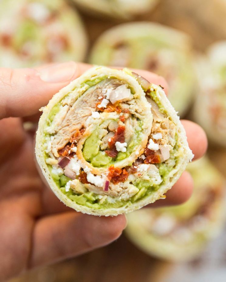 closeup shot of chicken avocado pinwheel with more blurred in the background