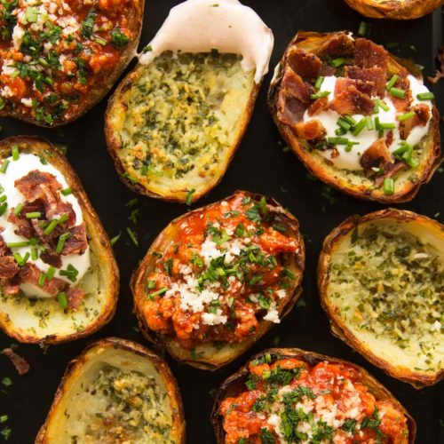 overhead shot of potato skins with fillings on oven tray