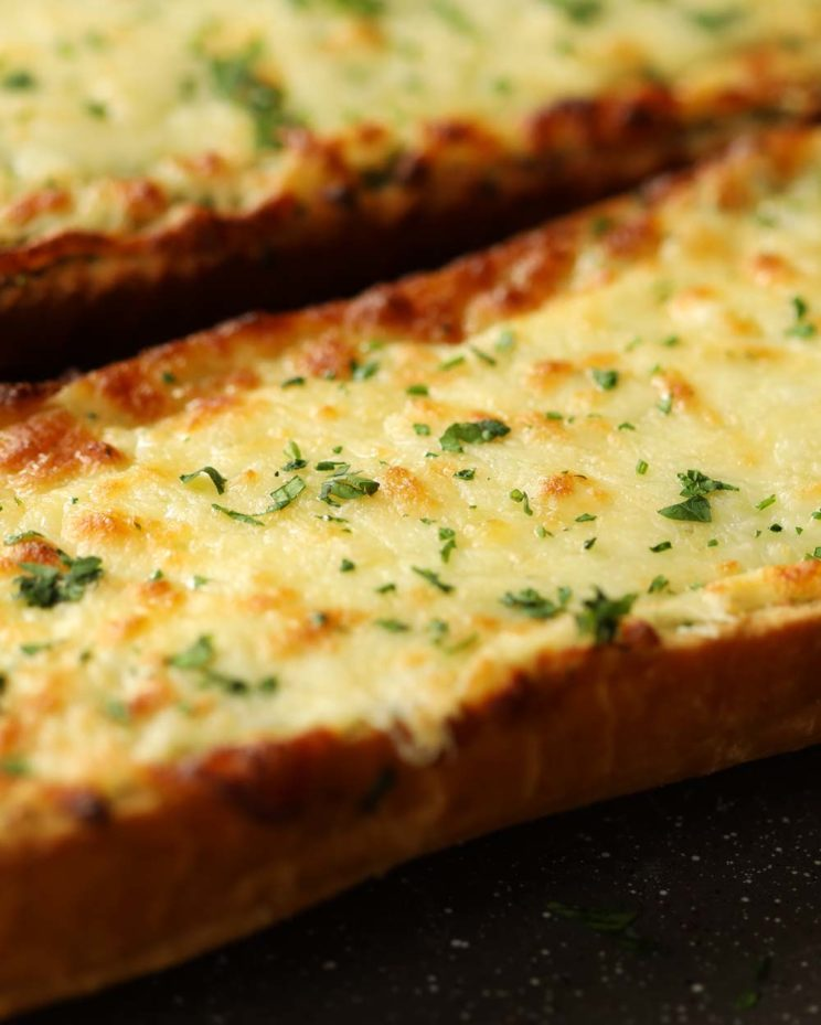 cheesy garlic bread fresh out the oven garnished with parsley