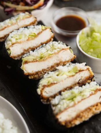 sushi sandwiches stacked on long plate with garnish surrounding