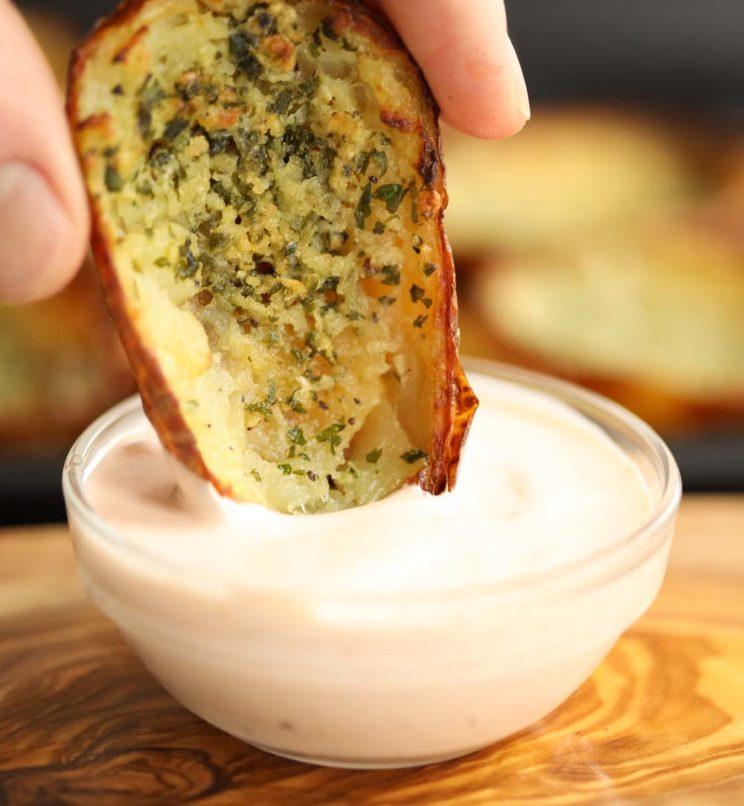 dipping potato skin into pot of sour cream
