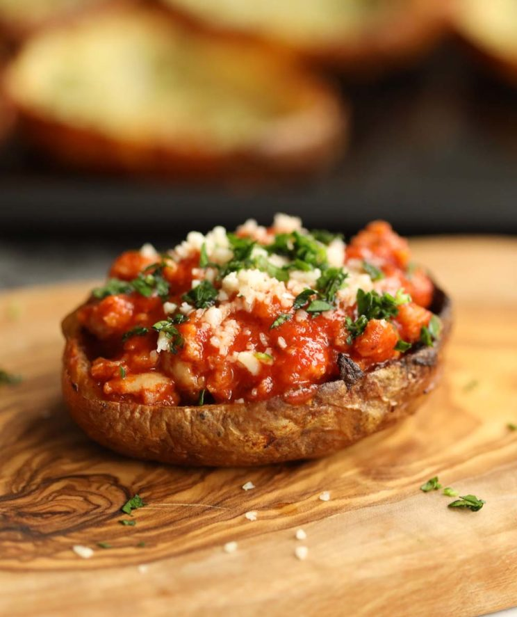 close up shot of bolognese in potato skin on chopping board garnished with parsley and parmesan