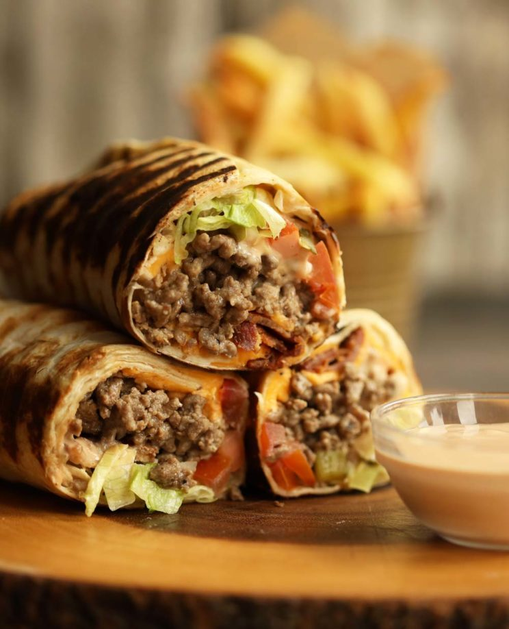 cheeseburger wraps stacked on top of each other on wooden board with fries blurred in background