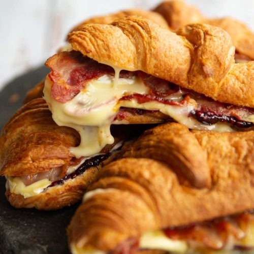 croissants stacked on one another with brie dripping off of top one