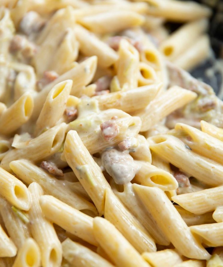 closeup shot of pasta in skillet with wooden spoon blurred in background