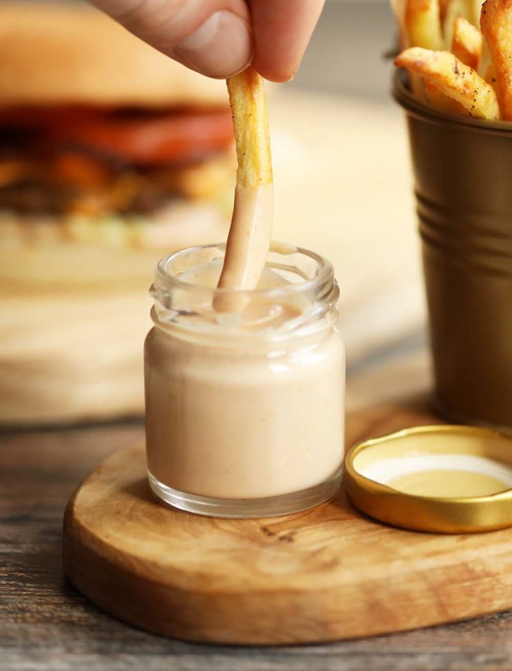 dunking french fries into small glass pot of burger sauce