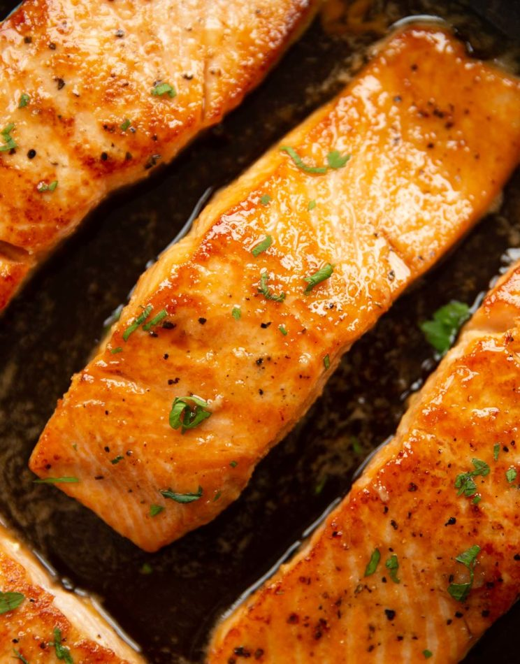 overhead shot of salmon fillets in pan garnished with parsley