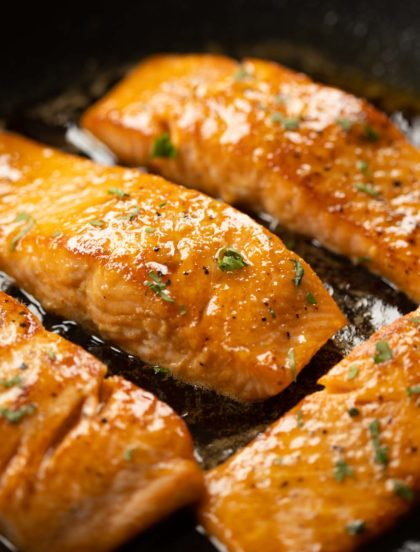 closeup of salmon in frying pan with glaze over it