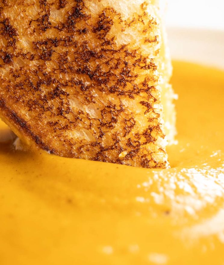 close up shot of dunking grilled cheese into soup