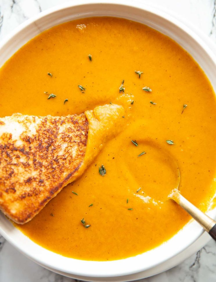 overhead shot of soup in a bowl with grilled cheese and spoon garnished with fresh thyme