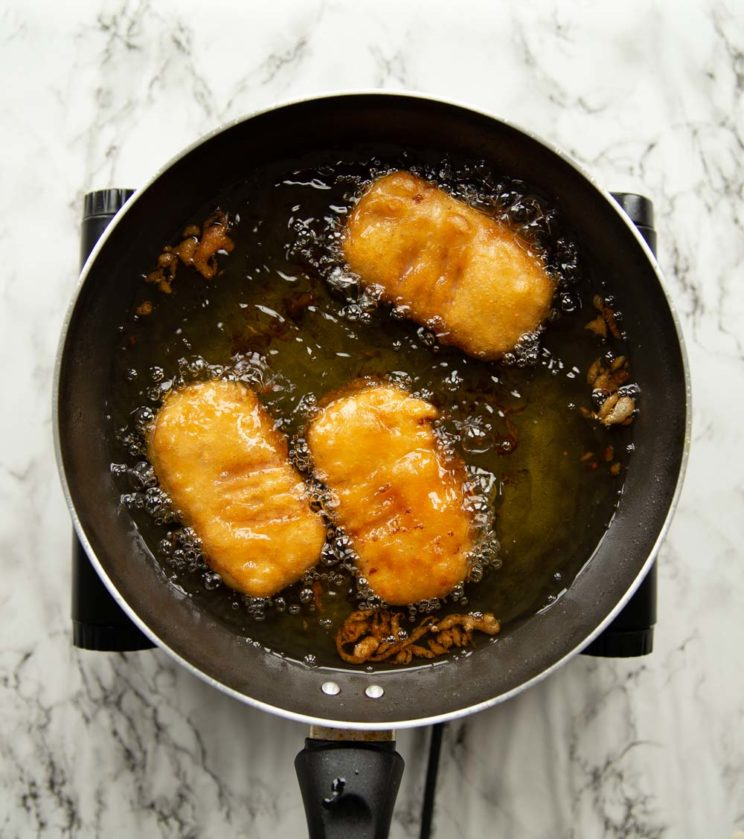 overhead shot of fritters deep frying in pot of oil