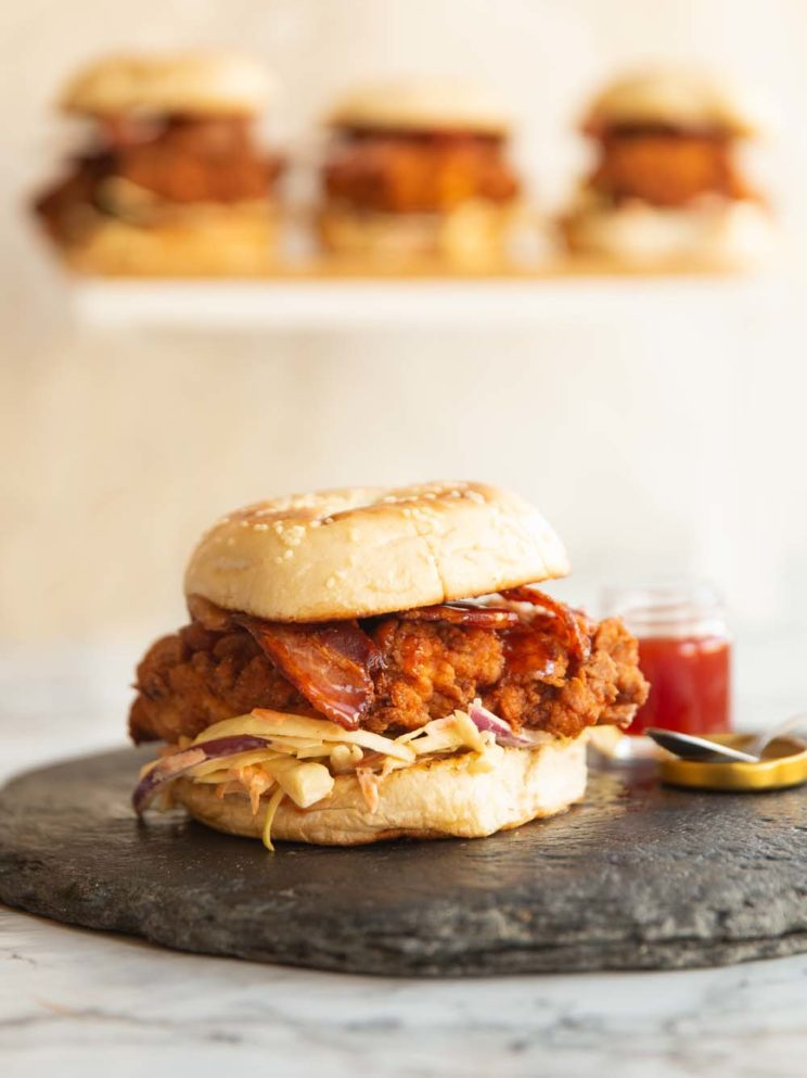 chicken burger on slate with 3 more levitated and blurred behind