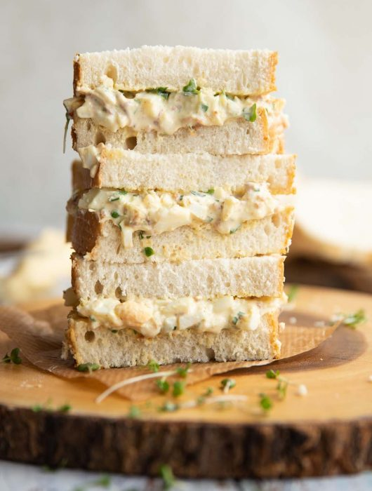 3 sandwiches stacked on each other on wooden board garnished with cress