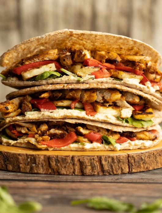 pitas stacked on each other on wooden board garnished with spinach leaves