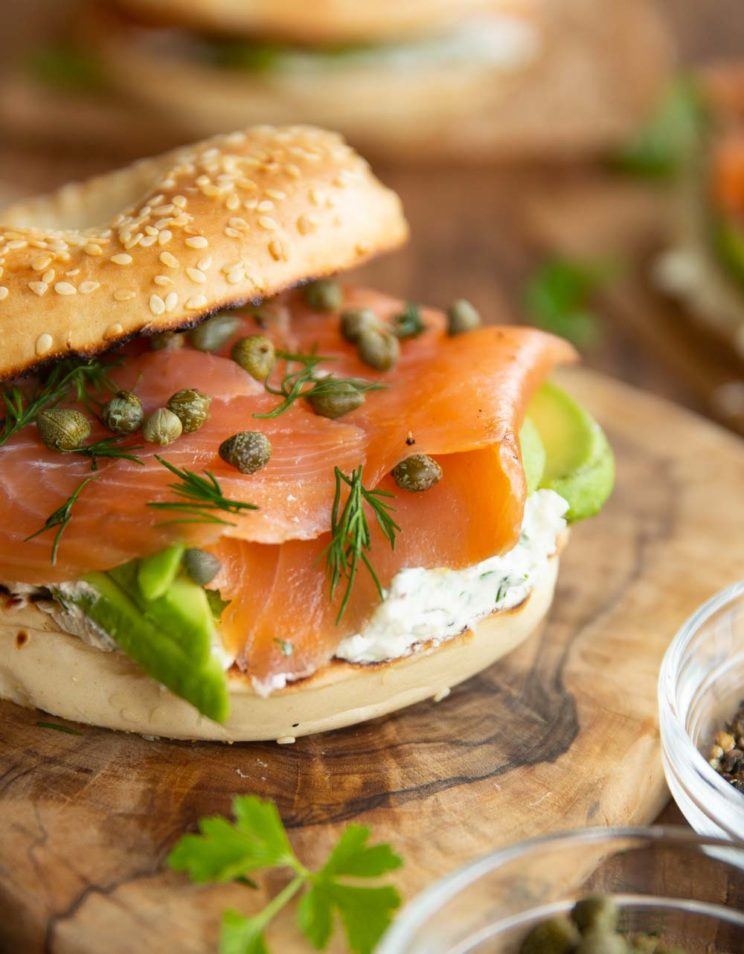 closeup shot of bagel with top resting on side with focus on salmon and capers