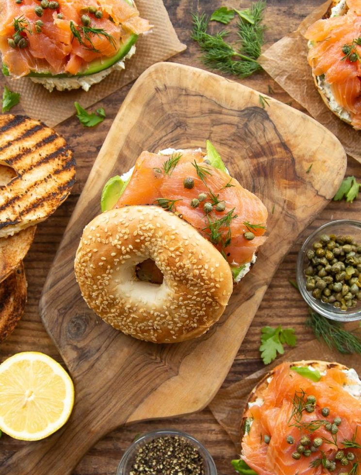 overhead shot of bagels on wooden board surrounded by ingredients and garnish