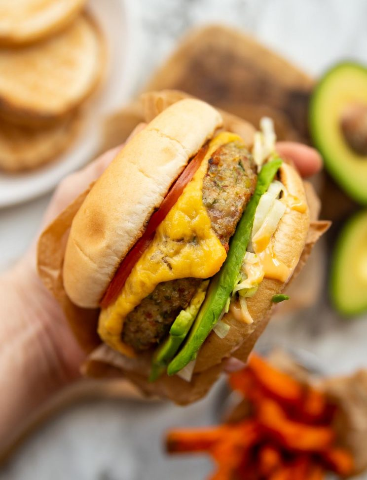 holding burger above chipping board with buns, avocado and sweet potato fries blurred behind