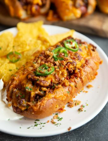 chili dog on white plate served with tortilla chips and more chili dogs blurred in background