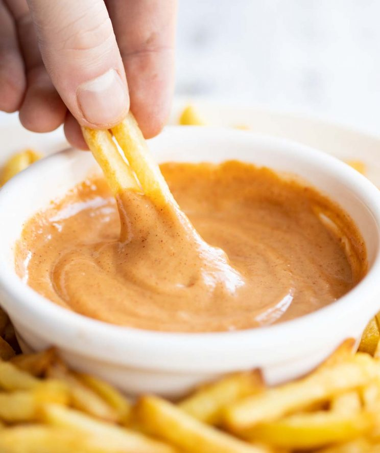 hand dunking french fries into bbq mayo