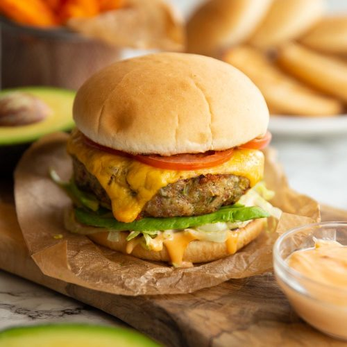 burger in wooden chopping board with buns and sweet potato fries blurred in background