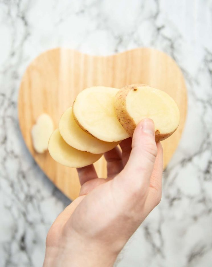 hand holding sliced potatoes above heart shaped chopping board