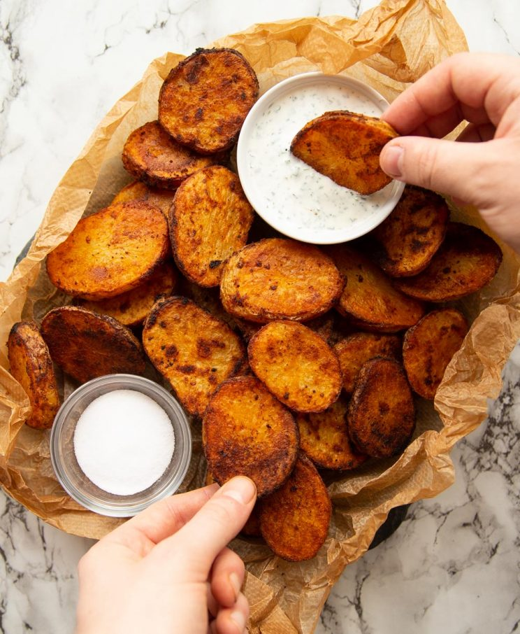overhead shot of potatoes un scrunched paper with pot of dip and salt with hands reaching in