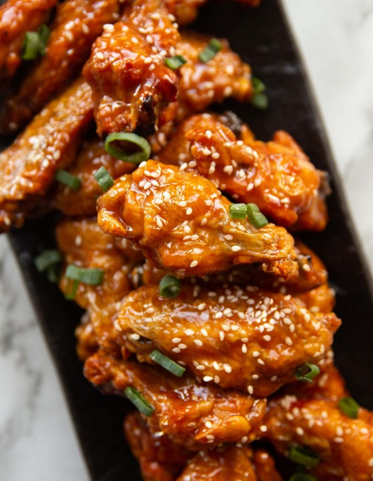 overhead shot of chicken wings stacked on rectangular slate plate