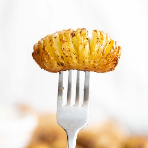 mini potato on end of fork with white background