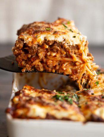 spatula lifting spaghetti from casserole dish