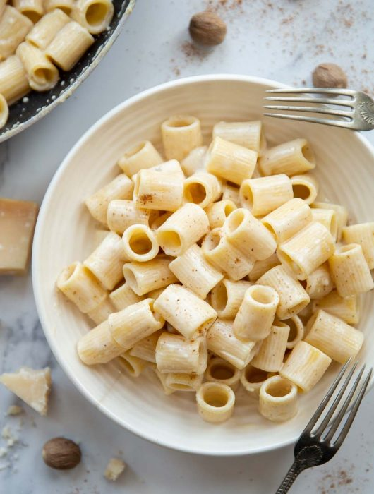 overhead shot of pasta in white bowl with parmesan and whole nutmegs garnished around