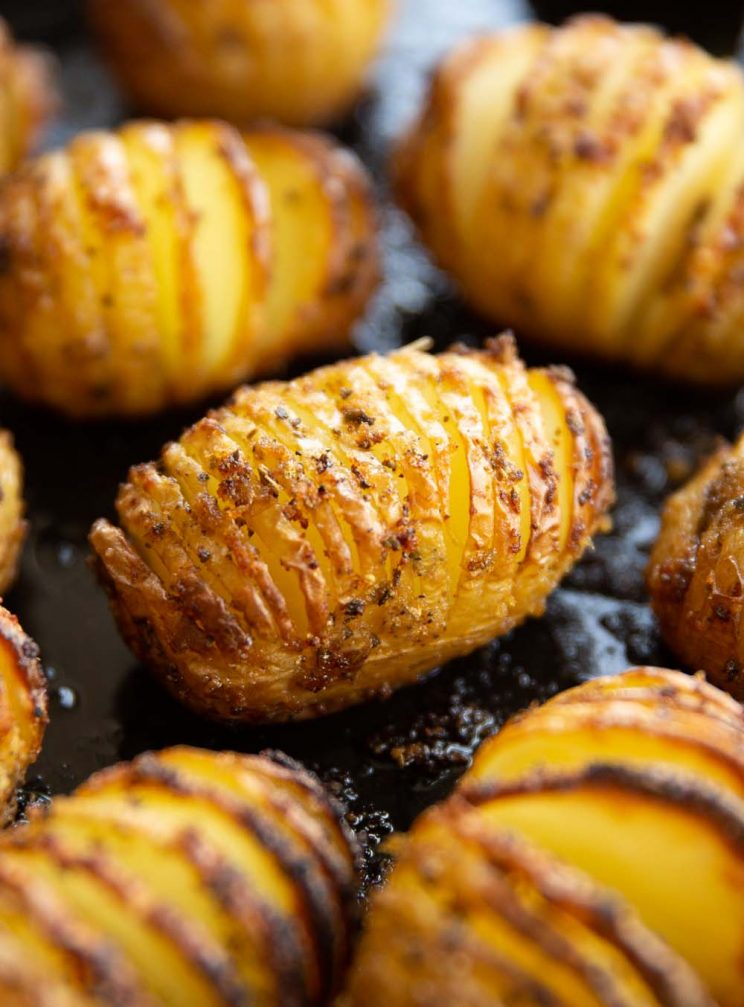 closeup shot of hasselback potatoes on black baking tray fresh out the oven