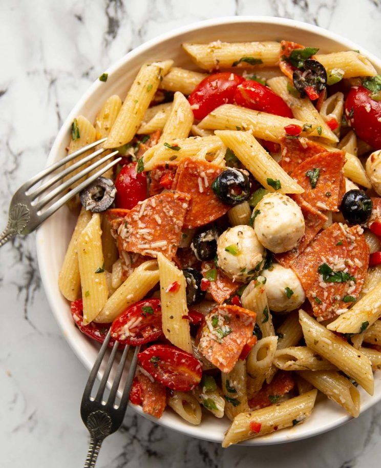 overhead shot of pasta in white bowl with two forks resting