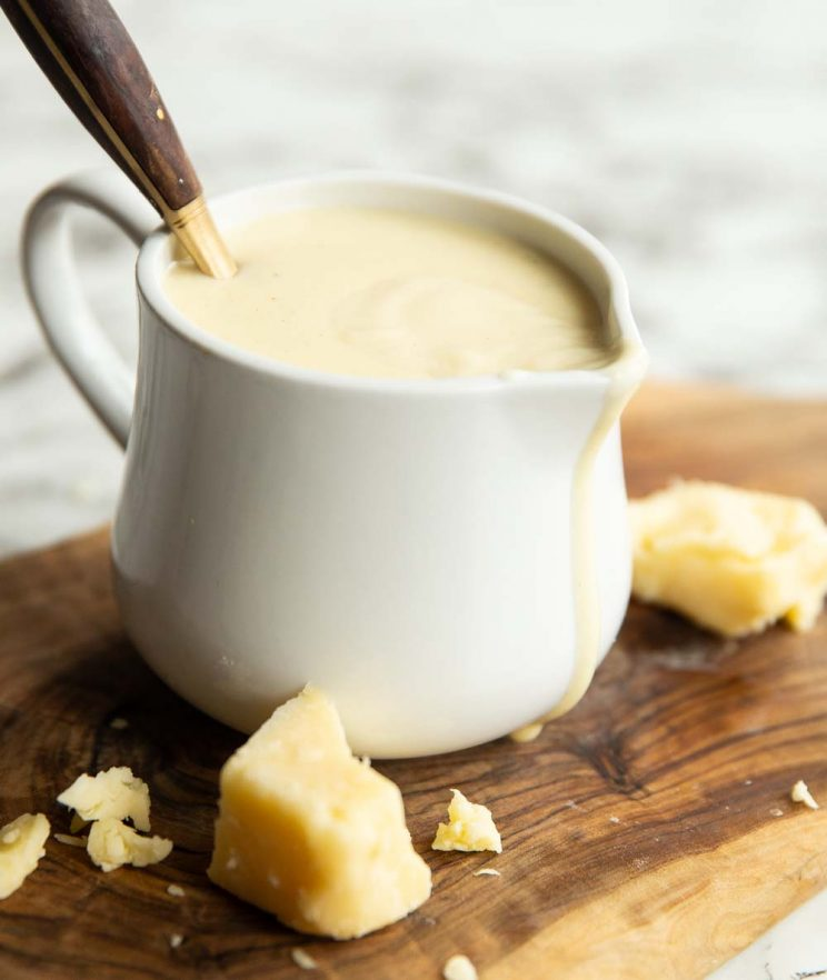cheese sauce in small white jug with gold spoon digging in
