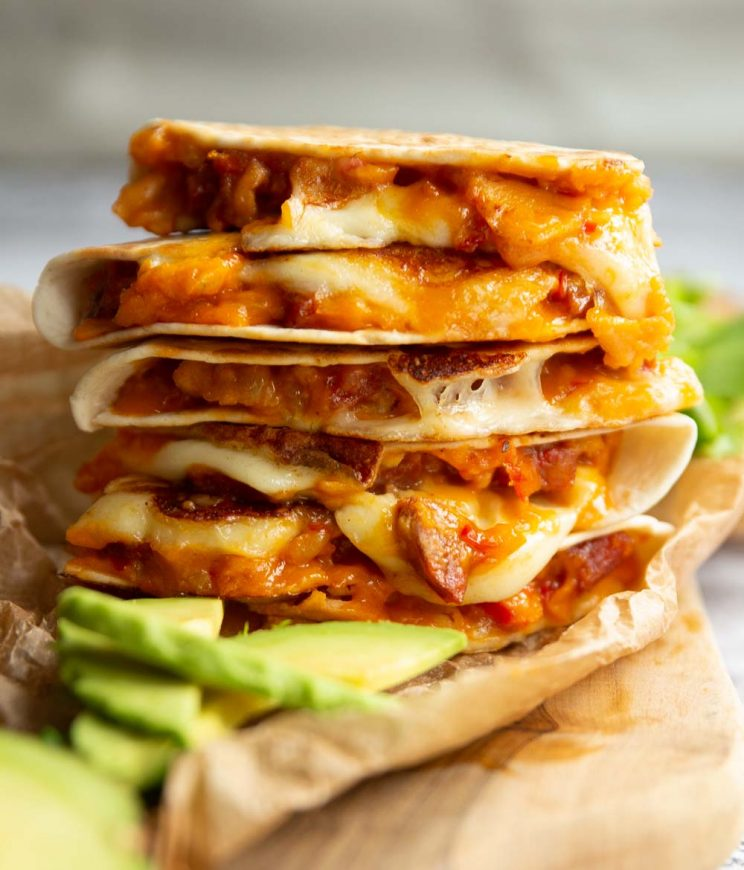 quesadillas stacked on each other on wooden board served with avocado slices and side salad