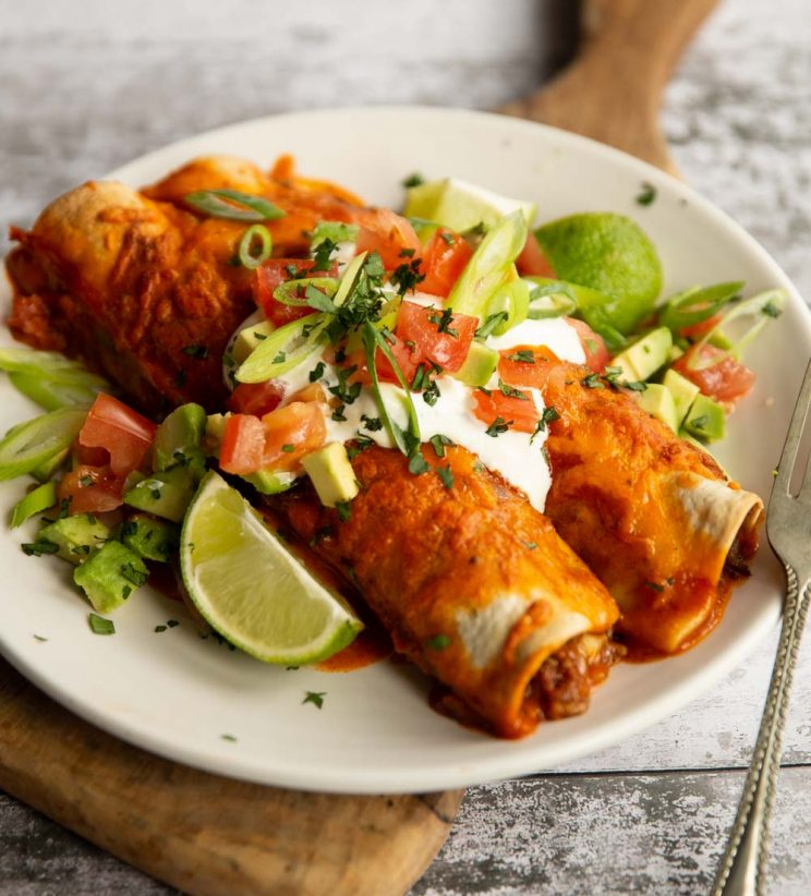 two enchiladas on white plate with sour cream and other toppings
